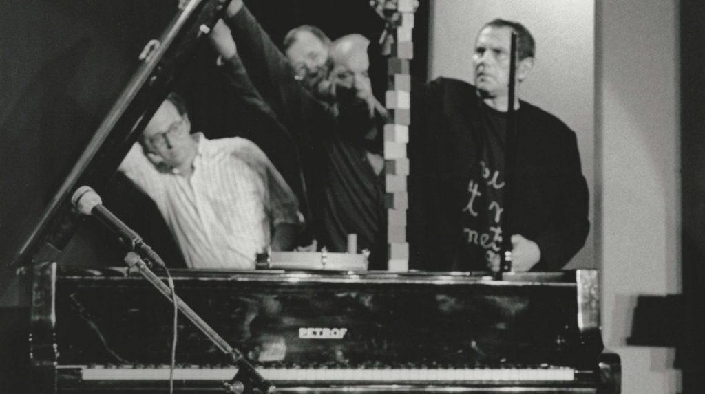 "George Brecht Incidental Music 1961. Performed by Ken Friedman, Geoff Hendricks, Al Hansen, and Ben Vautier (left to right) at ""Milano Poesia"", Ansaldo, Milan, 1989. Photo: F. Garghetti. Courtesy of Fondazione Bonotto. Copyright © Fabrizio Garghetti. All Rights Reserved."