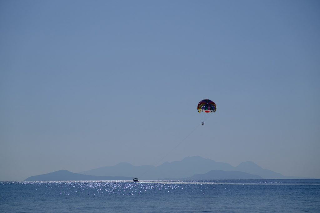 23 October 2020, Greece, Kefalos: Tourists hang on a parasailing parachute and let themselves be towed by a boat across the sea at Kefalos off the island of Kos in Greece. Photo: Robert Michael/dpa-Zentralbild/ZB